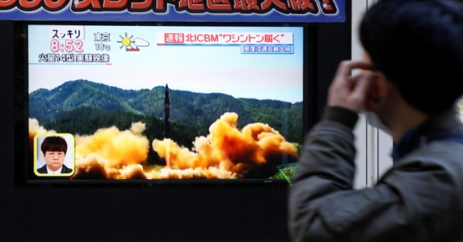 A man looks at a street monitor showing a news report about North Korea's missile launch, in Tokyo