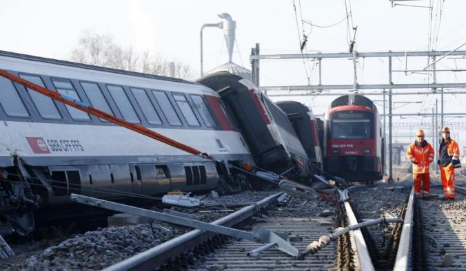 Rescue workers stand next to a derailed train after two trains collided near Rafz